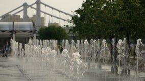 Strålar av vatten på en springbrunn i parkerar stock video
