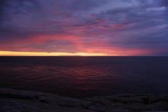 Strålarna av solen, efter solnedgången reflekterade i himlen och havet Fotografering för Bildbyråer
