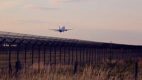 Strålen för passagerarenivå som tar av över säkerhetsflygplatsstaketet på solnedgången Arkivbilder