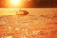 Strålen skidar är på den havsvattnet och solnedgången arkivbild