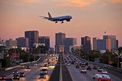Strålflygplan på landninginställningen som lågt flyger över stadsmotorväg Arkivfoton