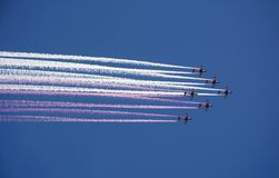 Strålkämpe av ljus-bredd flygplan med kulör rök royaltyfria bilder