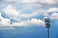 Strålkastare, strålkastare i stadion, och blåa himlar och moln arkivfoton