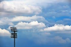 Strålkastare, strålkastare i stadion, och blåa himlar och moln arkivbilder