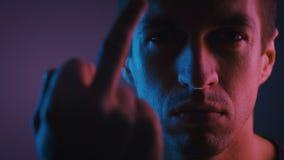 Strålkastare som visar dig i nyljus Aggressivt inställd man visar ett mellangärde i ett mörkt rum som tänds med neon arkivfilmer