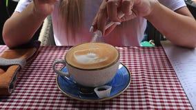 Strålningskänsliga händer som sätter socker på en kaffekopp och en sträng, i ett kafé stock video