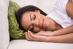 Strålningskvinna som sover på soffan i vardagsrum Royaltyfri Bild