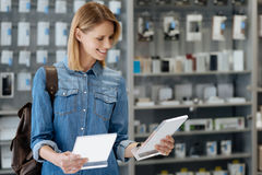 Strålningskvinnlig shoppare som jämför två informationsplattor om produkt Arkivbild