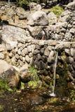Ström av sötvatten som kommer ut ur en metallutloppsrör från en springbrunn arkivfoton