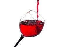 Ström av vin som hälls in i ett isolerat exponeringsglas Royaltyfria Bilder