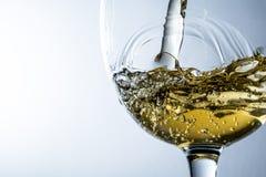 Ström av vitt vin som häller in i ett exponeringsglas, färgstänk för vitt vin på grå bakgrund arkivfoton