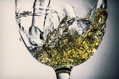 Ström av vitt vin som häller in i ett exponeringsglas, färgstänknärbild för vitt vin Svartvitt foto med färg av vin arkivbild