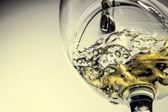 Ström av vitt vin som häller in i ett exponeringsglas, färgstänknärbild för vitt vin Svartvitt foto med färg av vin arkivbilder
