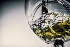 Ström av vitt vin som häller in i ett exponeringsglas, färgstänknärbild för vitt vin Svartvitt foto med färg av vin royaltyfri foto