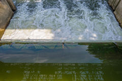 Ström som flödar till och med en dammbyggnad i solljus Royaltyfria Bilder