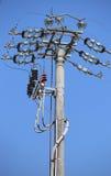 strömbrytare av en över huvudet kraftledning med den konkreta polen och väljer royaltyfria foton