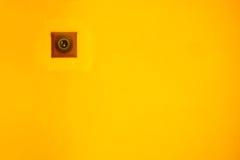 Strömbrytare på en gul vägg arkivfoto
