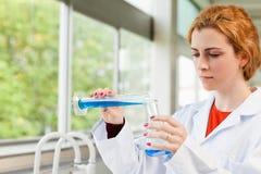 Strömende Flüssigkeit des Red-haired Wissenschaftlers stockbild