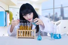 Strömende Flüssigkeit des schönen Wissenschaftlers am Labor lizenzfreies stockfoto
