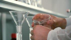 Strömende Flüssigkeiten des Chemikers in eine Flasche durch Trichter stock footage