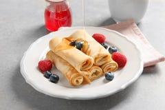 Strömender Honig auf dünnen Pfannkuchen mit Beeren Lizenzfreie Stockbilder