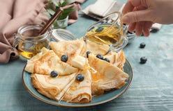 Strömender Honig der Frau auf dünnen Pfannkuchen mit Beeren Lizenzfreies Stockbild