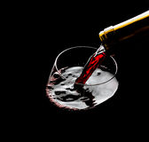 Strömender Rotwein in das Glas gegen schwarzen Hintergrund Stockfotografie