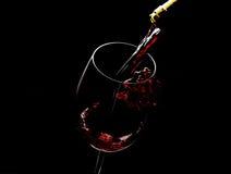 Strömender Rotwein in das Glas gegen schwarzen Hintergrund Lizenzfreie Stockbilder
