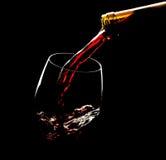 Strömender Rotwein in das Glas gegen schwarzen Hintergrund Stockbilder