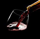 Strömender Rotwein in das Glas gegen schwarzen Hintergrund Stockbild