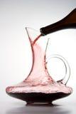 Strömender Rotwein in Dekantiergefäß Lizenzfreie Stockfotos
