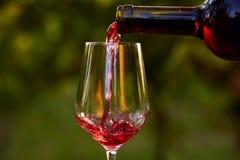 Strömender Rotwein in Glas lizenzfreie stockfotografie