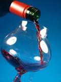 Strömender Rotwein von einer Flasche Stockfotos