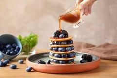 Strömender Sirup der Frau auf geschmackvolle Pfannkuchen mit Beeren auf Platte lizenzfreie stockfotografie