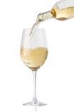 Strömender weißer Wein in ein Glas Stockbild
