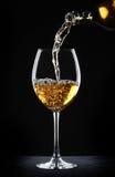 Strömender weißer Wein in ein Glas Stockbilder