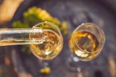 Strömender weißer Wein in Gläser lizenzfreie stockbilder