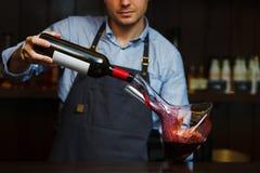 Strömender Wein des Sommelier in Glas vom Dekantiergefäß Männlicher Kellner Lizenzfreie Stockfotografie