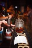 Strömender Whisky des Barmixers an der Stange Lizenzfreies Stockbild