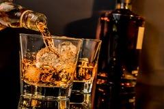 Strömender Whisky des Kellners vor Whiskyglas und -flaschen Lizenzfreie Stockbilder