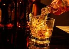 Strömender Whisky des Kellners vor Whiskyglas und -flaschen Stockfotografie