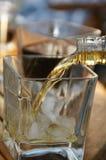 Strömender Whisky im Glas Lizenzfreie Stockbilder