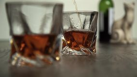 Strömender Whisky in zwei Gläsern stock footage