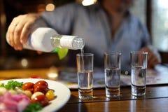 Strömender Wodka des Mannes im Pub Lizenzfreie Stockfotografie