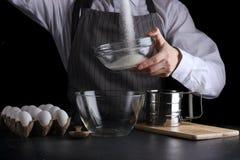 Strömender Zucker des Mannes in der Schüssel auf schwarzem Hintergrund Torte, die Konzept macht stockfoto