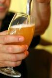 Strömendes Bier auf einem Glas Stockbild