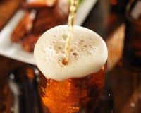 Strömendes Bier in Glas Stockbild