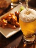Strömendes Bier mit Hühnerflügeln im Hintergrund. Stockfoto