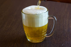 Strömendes Bier von der Flasche in Becher an der Bar Stockfoto
