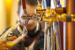 Strömendes Bier zu einem Glas Stockbild